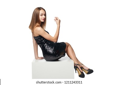 Full length smiling girl in sequined dress sitting on big white box with blank copy space looking at camera over shoulder, isolated on white background