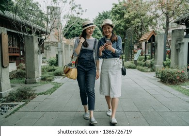 full length of smiling happy young girl friends travelers walking in old street path surrounding by japanese local traditional shop store. asian women searching online direction on map by smartphone