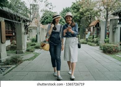 日本の伝統的な店の周りを取り囲む古い道を歩く旅人たちの笑顔で幸せな若い女の子の友達が、満身の長さで歩いている。スマートフォンで地図上の方向を探すアジアの女性