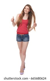 Full length of smiling leggy young female in denim shorts and red top showing double thumb up, isolated on white background