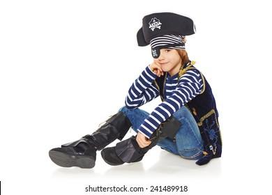 Full length smiling little boy wearing pirate costume sitting on the white studio floor, over white background