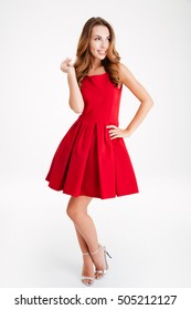 Full length of smiling playful young woman in red dress standing and looking up over white background