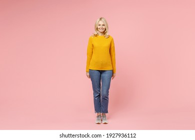 Full length of smiling pretty elderly gray-haired blonde woman lady 40s 50s years old wearing yellow basic sweater standing and looking camera isolated on pastel pink color background studio portrait