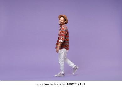Full length smiling young african american man in casual colorful shirt hat walking step look camera isolated on violet background studio portrait. People emotions lifestyle concept. Mockup copy space