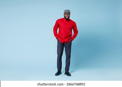 Full length of smiling young bearded african american man in casual red shirt cap eyeglasses standing holding hands crossed in pockets looking aside isolated on pastel blue background studio portrait