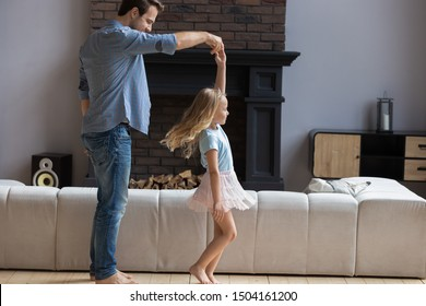 Full length smiling young father twisting happy little preschool blonde daughter. Overjoyed family of daddy and kid girl dancing together, enjoying leisure weekend time in living room at home.
