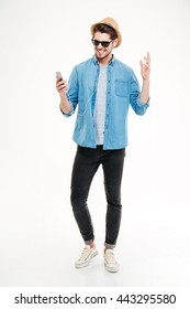 Full length of smiling young man listening to music from smartphone over white background