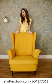 Full length of a smiling young pin up woman in yellow dress standing behind chair and looking at camera