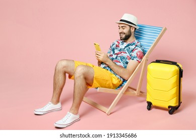 Full length smiling young traveler tourist man in hat sit on deck chair using mobile cell phone typing sms message isolated on pink background. Passenger travel on weekend. Air flight journey concept - Shutterstock ID 1913345686
