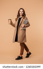 Full length of a smiling young woman wearing a coat walking isolated over beige background, carrying laptop and drinking coffee