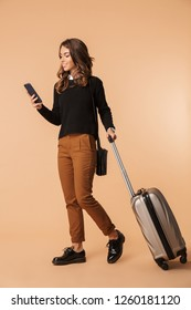 Full length of a smiling young woman wearing a sweater walking with a travel bag isolated over beige background, holding mobile phone
