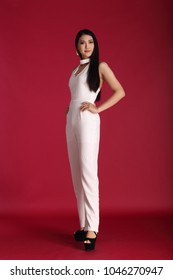 Full length snap figure, Beautiful Asian Long straight black hair transgender woman in white slack dress, fashion make up, studio lighting red background copy space