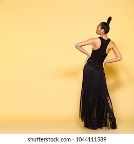 Full length Snap figure of Young Fashion Model Woman black evening gown hair style looking an idea and pointing to left side copy space area for text ads, Studio Lighting beige yellow background