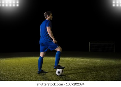Full length of soccer player standing on ground with his foot over a soccer ball