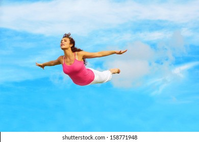 Full length of a sporty female flying in air with hands outstretched against sky.