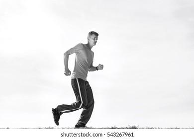 Full length of sporty man jogging against sky