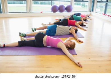 Full length of sporty people stretching on mats at yoga class in fitness studio