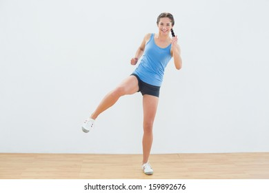 Full length of a sporty young woman stretching leg in fitness center