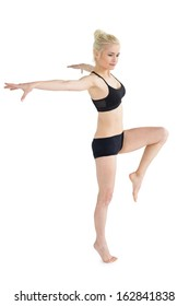 Full length of a sporty young woman balancing on one leg while stretching out hands over white background