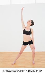 Full length of a sporty young woman stretching hand in fitness studio