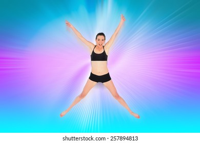 Full length of a sporty young woman jumping against abstract background