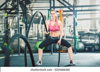 Full length of a strong and beautiful woman waving battle ropes with alternative motion during functional training workout at the gym