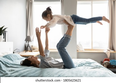 Full length strong young smiling mommy lying on comfortable bed, holding small kid daughter on straight legs. Happy little child girl flying in air, practicing yoga activity with mother in bedroom.