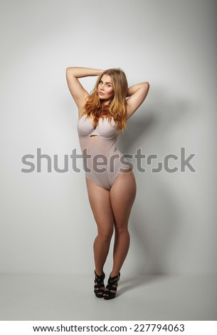 93397b27250 Full length studio image of beautiful voluptuous woman in body stockings  standing on grey background. Sexy young plus size female model posing in  underwear.