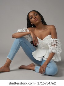 Full length studio portrait of african young woman with long black african pigtails wearing blue jeans and white top and sitting at gray background