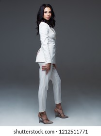 Full length studio portrait of attractive caucasian woman with dark hair in white suit standing on plain grey background, vertical. Bossy female, job interview concept, confident independent lady