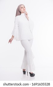 Full length studio portrait of beautiful young girl with hijab in white outfit and high heel shoes on plain white background.