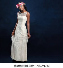 Full length studio portrait of beautiful young african bride in long white wedding gown. Woman wearing colorful flower garland against dark blue background.