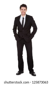 Full length studio portrait on white of a smiling confident young businessman standing with folded arms
