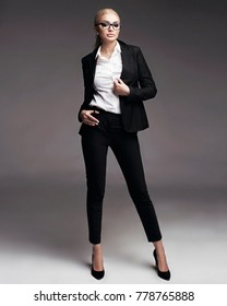Full length studio portrait of young business woman with blonde tightened hair in black suit, high heel shoes and white shirt, in eye glasses on plain grey background
