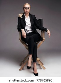 Full length studio portrait of young business woman with blonde tightened hair in black suit, high heel shoes and white shirt, in eye glasses, sitting in chair on plain grey background