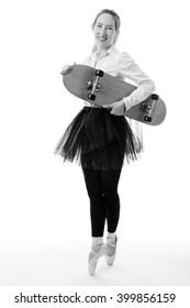 Full length studio shot of a ballerina business model en pointe whilst holding a skateboard in one hand.  isolated on white