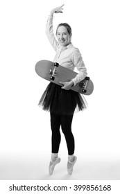Full length studio shot of a ballerina business model en pointe whilst holding a skateboard in one hand.