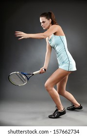 A full length studio shot of a female tennis player executing a forehand strike