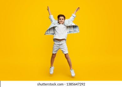 109230ca7f Full length stylish youngster with raised hands looking at camera and leaping  up against yellow background