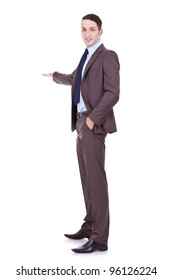 Full length of successful business man presenting over white background . young business man making a presentation and showing something