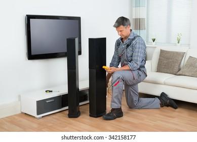 Full length of technician checking TV speaker with multimeter at home
