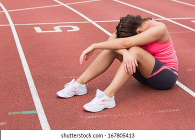 Full length of a tensed sporty woman sitting on the running track