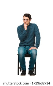 Full length of thoughtful businessman keeps hand under chin, seated on a chair isolated on white background. Business employee, wears glasses, looking focused thinking of solutions and new ideas.