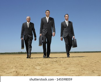 Full length of three businessmen with briefcases walking in desert