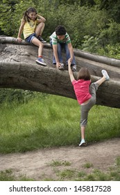 Full length of three friends climbing on fallen tree
