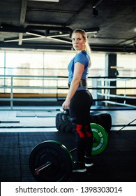 Full length three quarters portrait of determined woman wearing weightlifting belt and knee supporters standing near barbell with weight plates and looking at camera in gym