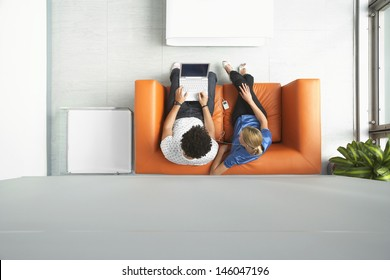 Full length top view of a man and woman using laptop on orange sofa in reception room at office
