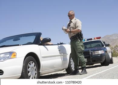 Full length of traffic officer writing ticket
