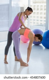 Full length of trainer assisting woman at fitness studio
