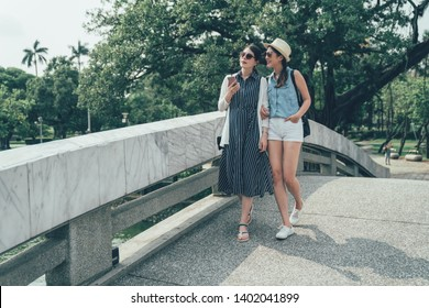 full length two asian friends having walk on bridge in chinese traditional park in taiwan taichung. young girls communicating and using mobile phones by nature pool. women travelers browse map app
